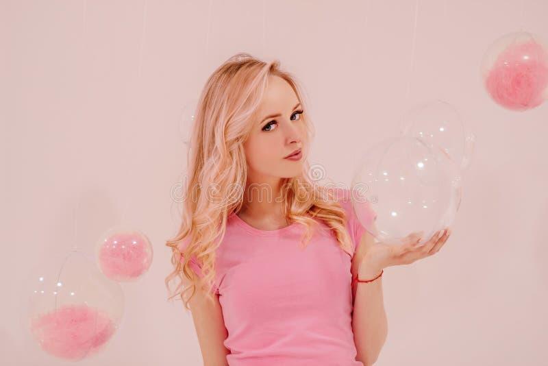 Muchacha rubia hermosa joven en rosa en el fondo blanco con las burbujas transparentes rosadas imagenes de archivo