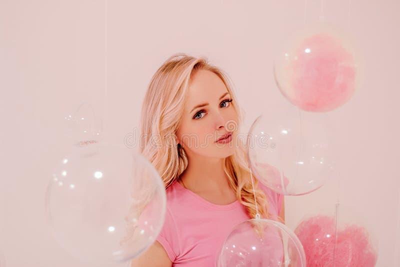 Muchacha rubia hermosa joven en rosa en el fondo blanco con las burbujas transparentes rosadas foto de archivo libre de regalías