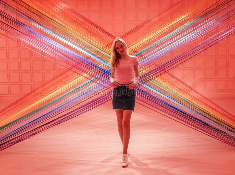 Muchacha rubia hermosa joven en un fondo rosado de hilos coloridos imagenes de archivo