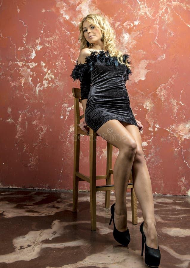 Muchacha rubia hermosa joven en un vestido de cóctel negro foto de archivo libre de regalías