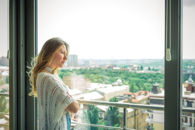 Muchacha rubia hermosa joven que se coloca en la ventana y triste imagen de archivo libre de regalías