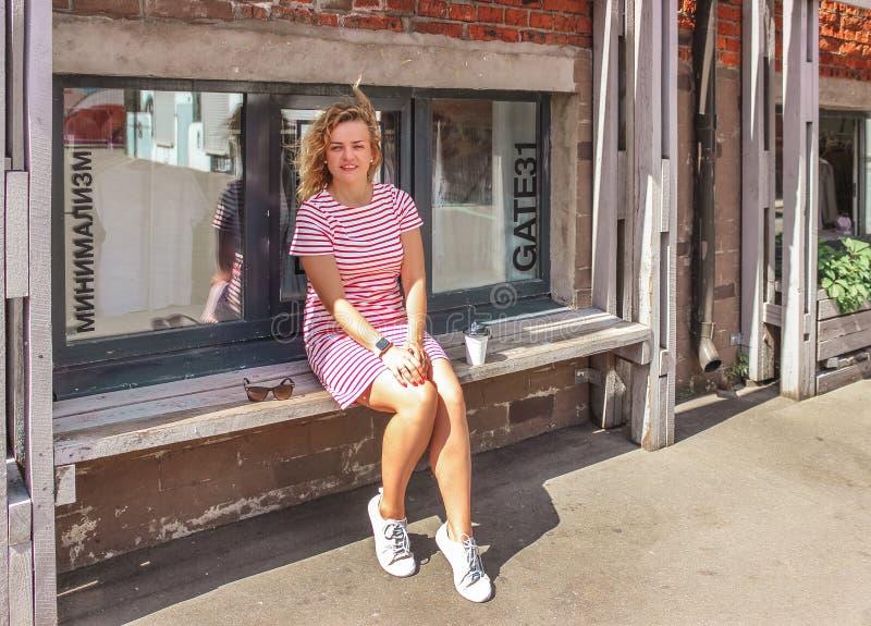 Muchacha rubia hermosa joven que se sienta en banco y el café de consumición de la mañana en ciudad grande foto de archivo
