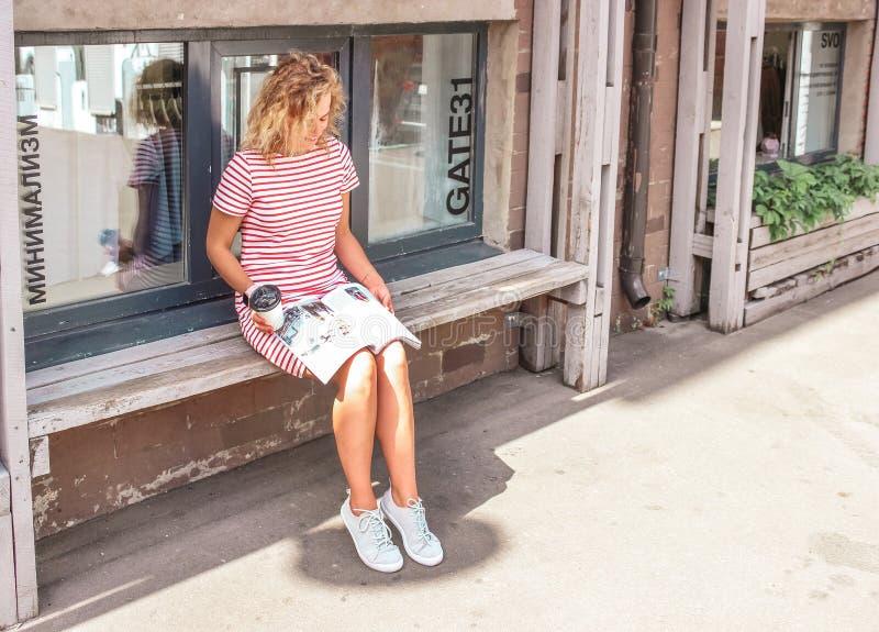 Muchacha rubia hermosa joven que se sienta en noticias de la moda de la lectura del banco en la revista y el café de consumición  imagenes de archivo