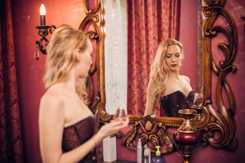 Muchacha rubia hermosa joven y su reflexión en un espejo viejo grande del gabinete de señora en el cuarto de lujo foto de archivo libre de regalías