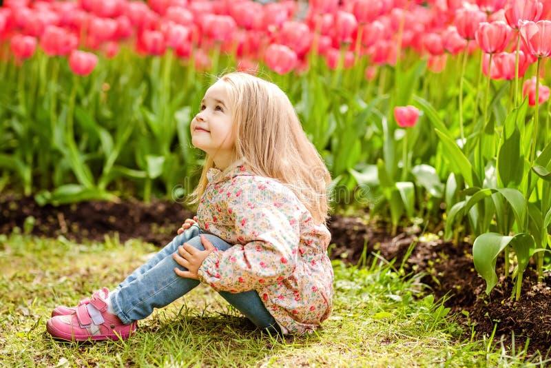 Muchacha rubia hermosa muy dulce en una capa rosada que se sienta cerca de imagen de archivo libre de regalías