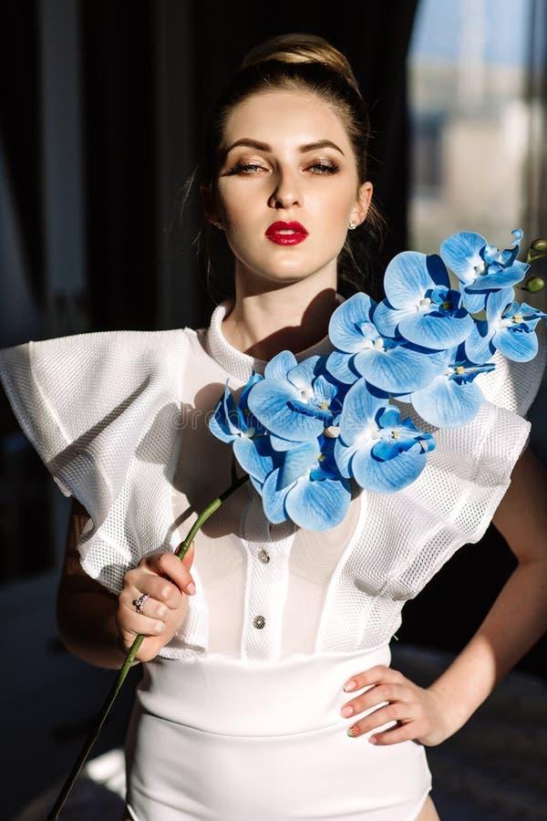 Muchacha rubia hermosa que sostiene las orquídeas, luz del sol dura, moda foto de archivo