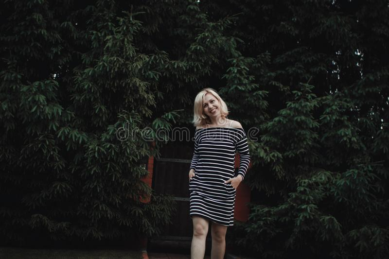 Muchacha rubia interesante elegante en un vestido rayado en una cerca de madera y un seto grueso de abetos Diversi?n y sonrisas l foto de archivo