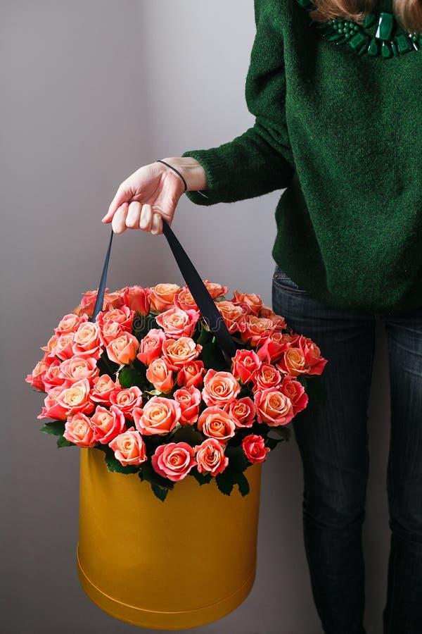 Muchacha rubia joven agradable oliendo florece sosteniendo el ramo de las rosas del melocotón en caja del sombrero contra la pare imagen de archivo libre de regalías
