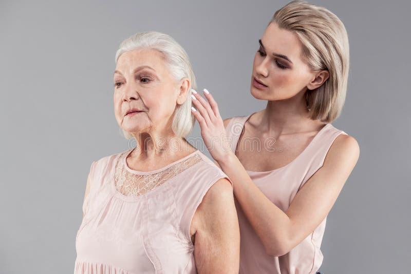 Muchacha rubia joven atenta que corrige el peinado de su vieja madre fotografía de archivo libre de regalías