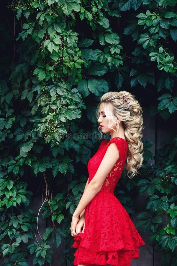 Muchacha rubia joven atractiva en el vestido rojo que presenta cerca de un viñedo salvaje imagenes de archivo