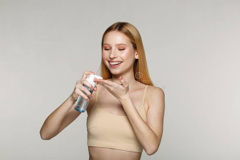 Muchacha rubia joven bonita con la piel perfecta que aplica la crema cosmética en su mano imágenes de archivo libres de regalías