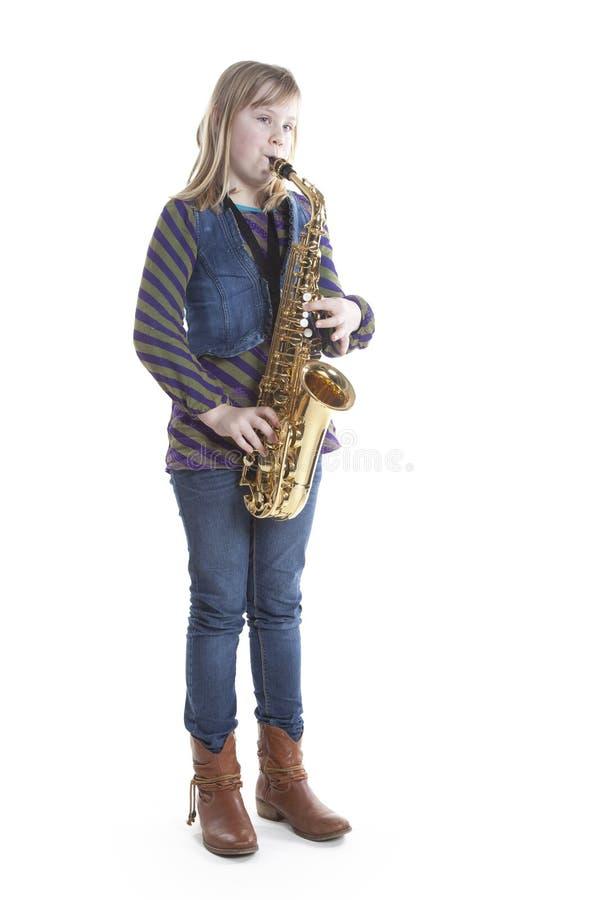 Muchacha rubia joven con el saxofón del alto en estudio imagenes de archivo
