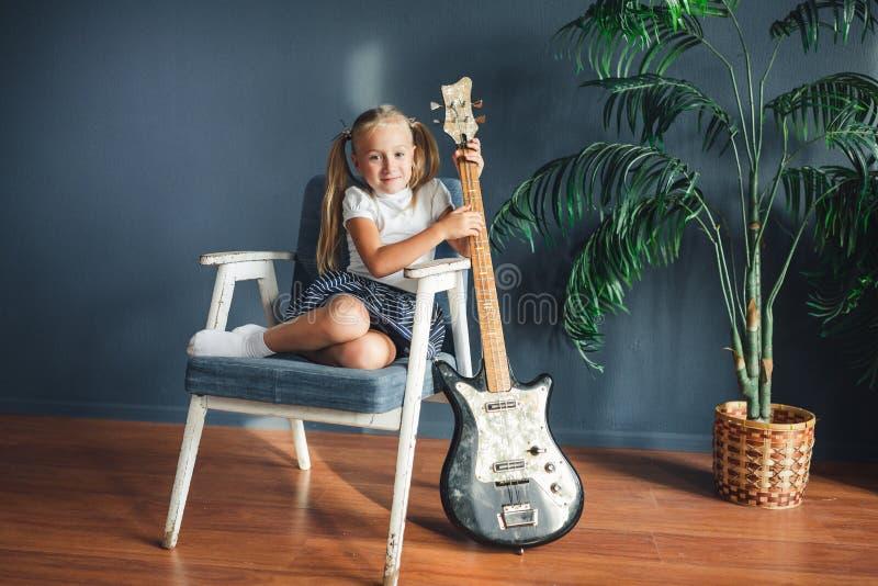 Muchacha rubia joven con las colas en la camiseta, la falda y las sandalias blancas con la guitarra eléctrica en casa que mira la imagenes de archivo