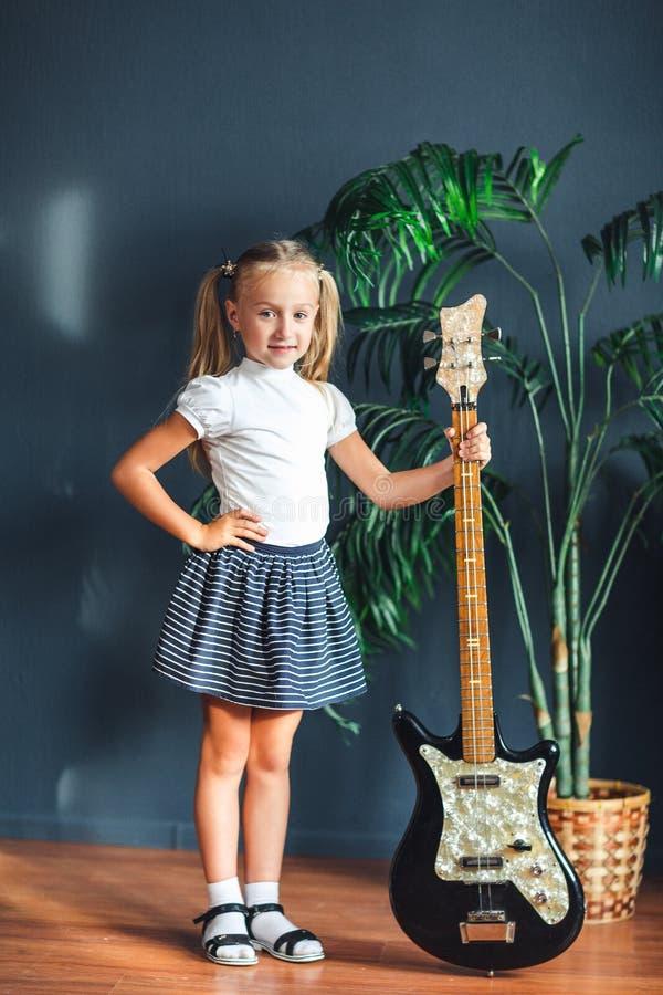Muchacha rubia joven con las colas en la camiseta, la falda y las sandalias blancas con la guitarra eléctrica en casa que mira la foto de archivo