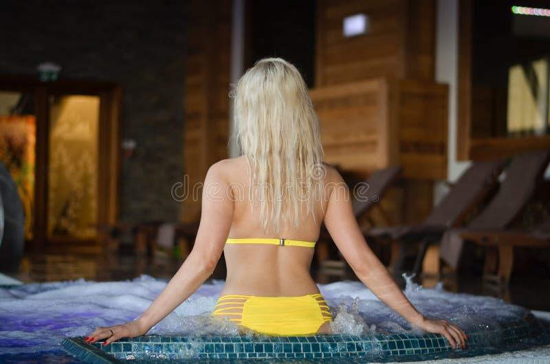 Muchacha rubia joven de c que se relaja en día de fiesta de las vacaciones del invierno del durig de la tina caliente del Jacuzzi foto de archivo libre de regalías