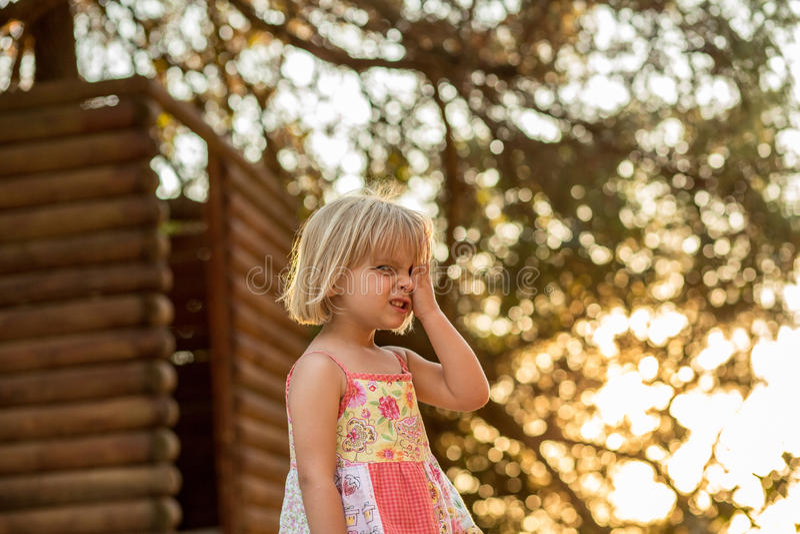 Muchacha rubia joven del niño que hace una cara al aire libre con el árbol grande en fondo Luz caliente de la puesta del sol Trav imagen de archivo