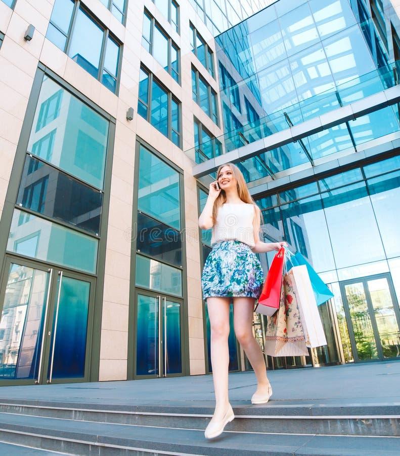 Muchacha rubia joven del retrato de la forma de vida, con los bolsos de compras saliendo de tienda y hablando por el teléfono móv imagenes de archivo