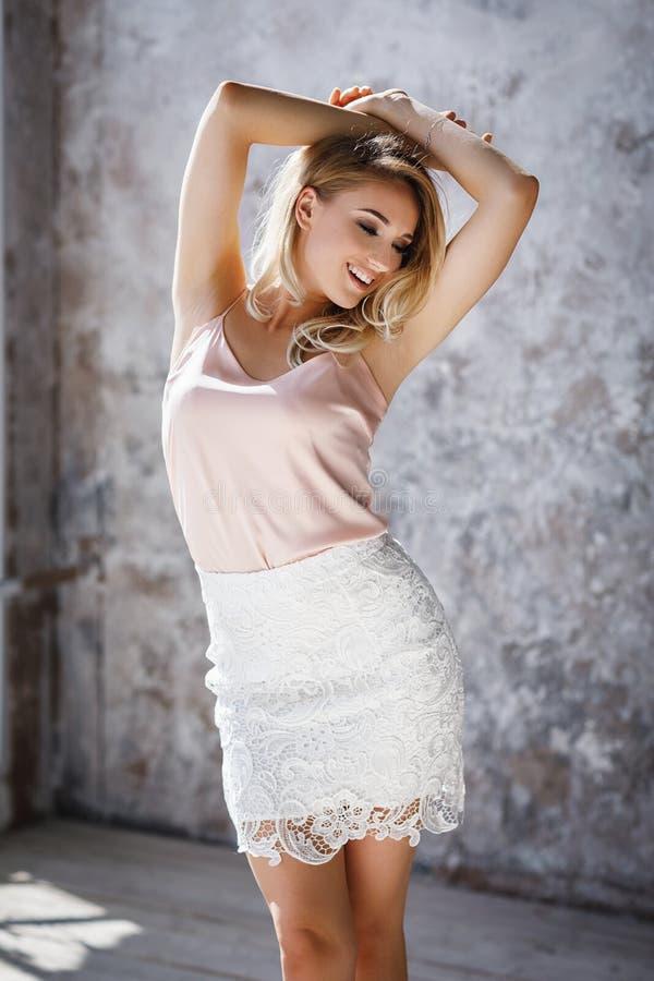 Muchacha rubia joven elegante hermosa que presenta en un cuarto imagen de archivo libre de regalías