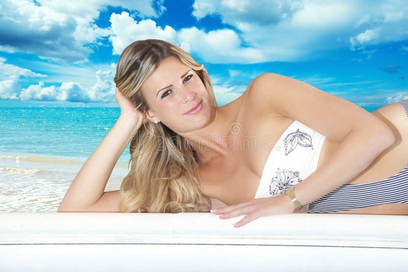 Muchacha rubia joven en el bikini que miente en una pared blanca Mar azul y playa tropical fotos de archivo