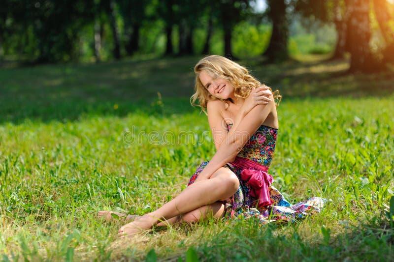 Muchacha rubia joven en el vestido colorido brillante que plantea la mentira en hierba en parque del verano en los rayos del sol  fotografía de archivo