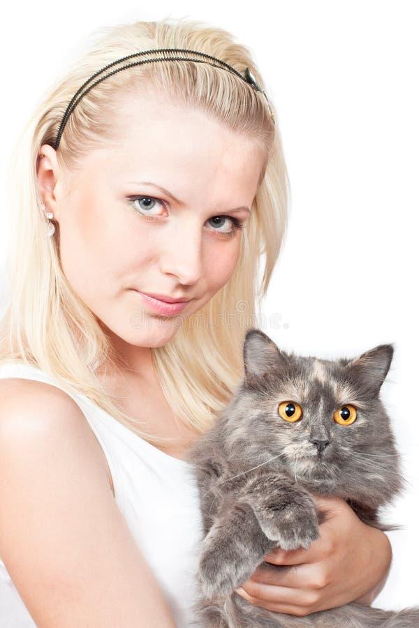 Muchacha rubia joven feliz y gato gris imagenes de archivo