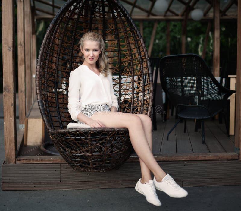 Muchacha rubia joven hermosa con las piernas largas que se sientan en una silla de mimbre en un café al aire libre en una tarde,  imagen de archivo