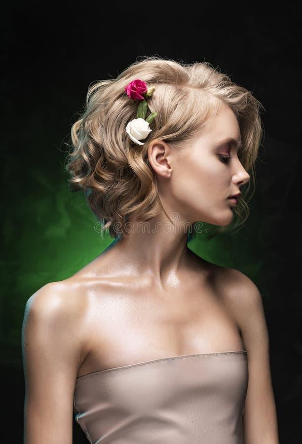 Muchacha rubia joven hermosa con los hombros desnudos, las flores trenzadas en su pelo y las actitudes aceitosas del cuerpo en un fotos de archivo