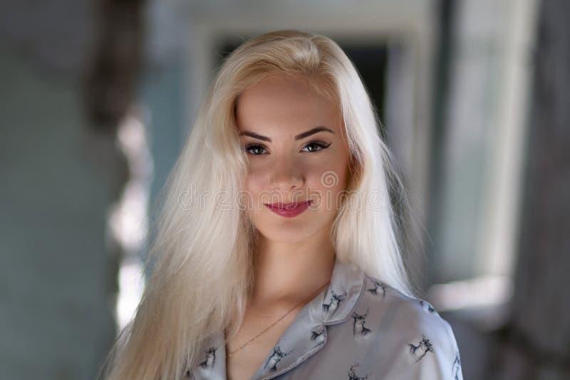 Muchacha rubia joven hermosa con una cara bonita y sonrisa hermosa de los ojos El retrato de una mujer con el pelo largo y sorpre fotografía de archivo