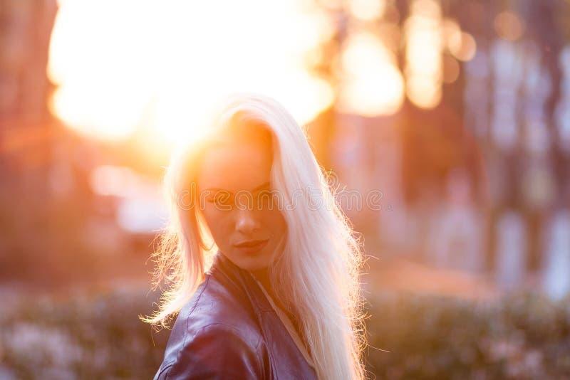 Muchacha rubia joven hermosa con una cara sonriente bonita y ojos hermosos Una mujer con el pelo largo disipa su, sorprendiendo m imagenes de archivo