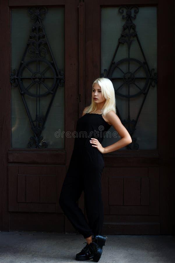 Muchacha rubia joven hermosa que presenta en el fondo de las puertas de Borgoña Mujer atractiva en una alineada negra La muchacha imagen de archivo libre de regalías