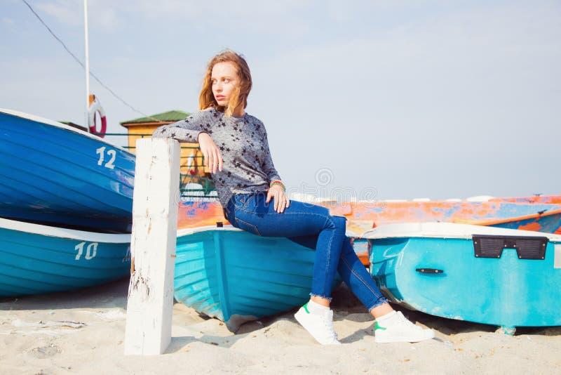 Muchacha rubia joven hermosa que se sienta en el barco azul en la playa foto de archivo libre de regalías