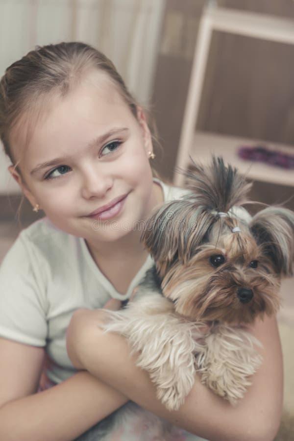 Muchacha rubia joven linda con su perrito del terrier de Yorkshire que juega y que abraza imagen de archivo