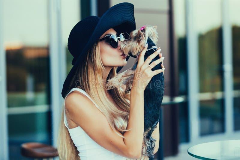 Muchacha rubia joven que besa el pequeño perro fotografía de archivo