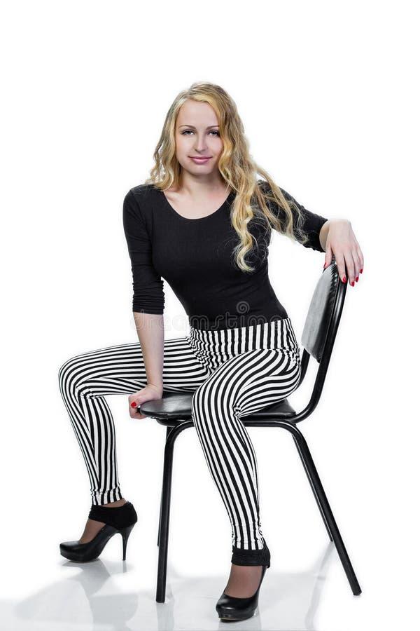 Muchacha rubia joven que presenta en silla imagen de archivo libre de regalías