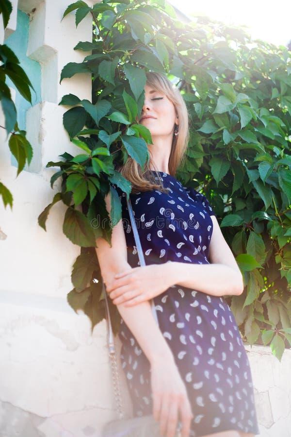 Muchacha rubia joven que se coloca cerca de la pared de las hojas imagen de archivo libre de regalías