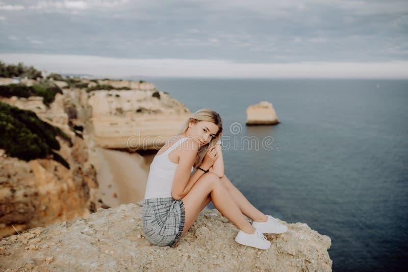 Muchacha rubia joven que se sienta al borde del acantilado que mira en el océano concepto del recorrido fotografía de archivo libre de regalías