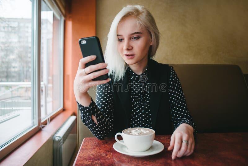 Muchacha rubia joven que se sienta en un café acogedor con una taza de café y que mira de cerca en el teléfono fotos de archivo