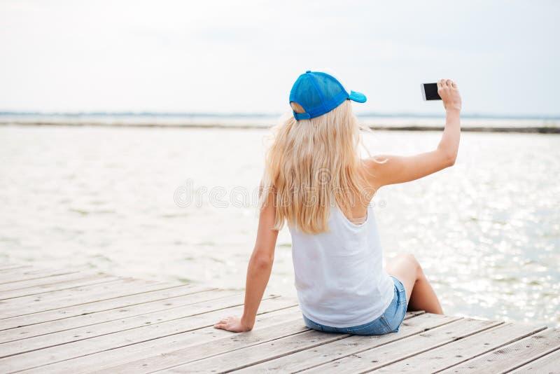 Muchacha rubia joven que toma el selfie con el teléfono en el embarcadero de madera imagen de archivo