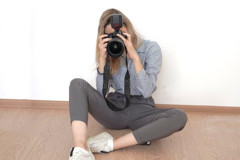 Muchacha rubia joven que toma las imágenes que se sientan en el piso en el estudio foto de archivo libre de regalías