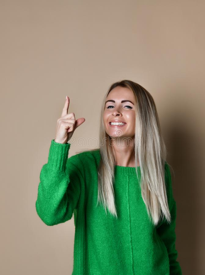 Muchacha rubia joven sonriente agradable en fondo beige que señala el finger hasta la atención del drenaje a la información impor foto de archivo