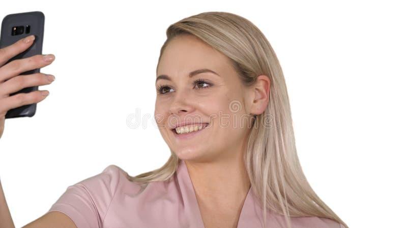 Muchacha rubia joven sonriente que toma un selfie en el fondo blanco fotos de archivo