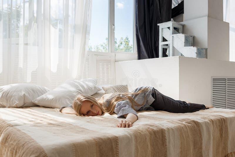 Muchacha rubia linda con el pelo largo en camisa rayada y las mentiras negras de los pantalones en cama en la cara del estudio ab imágenes de archivo libres de regalías