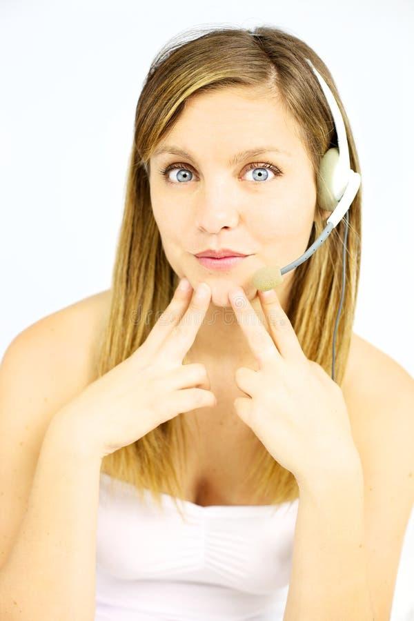 Muchacha rubia linda con los ojos azules y los auriculares imagen de archivo