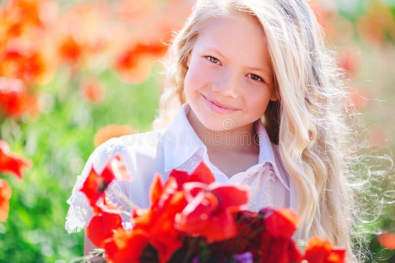 Muchacha rubia linda del niño con el ramo de amapolas fotos de archivo