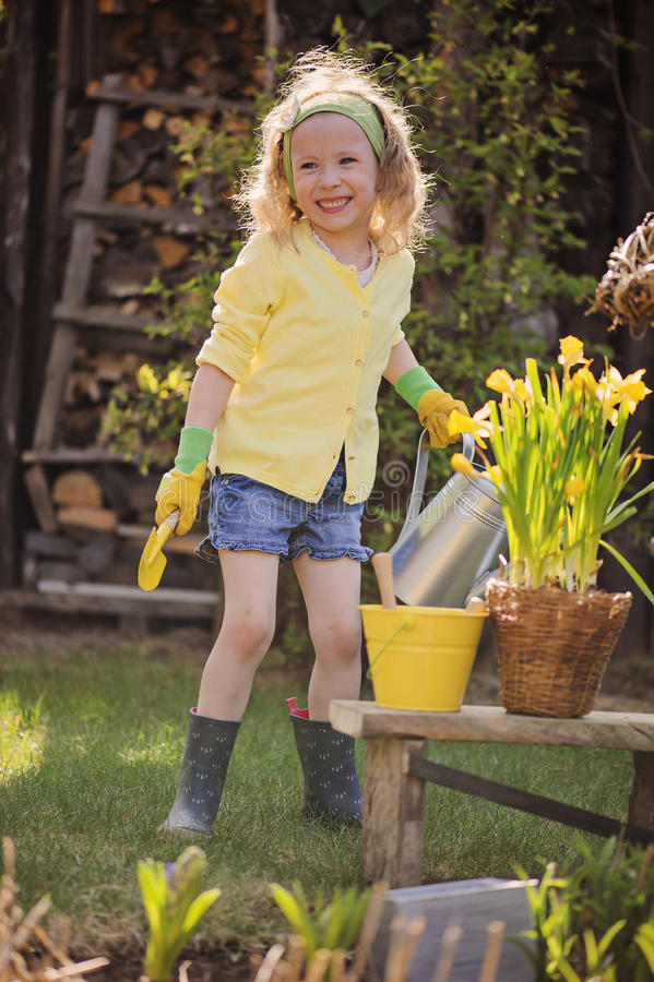 Muchacha rubia linda del niño que se divierte que juega al pequeño jardinero fotos de archivo