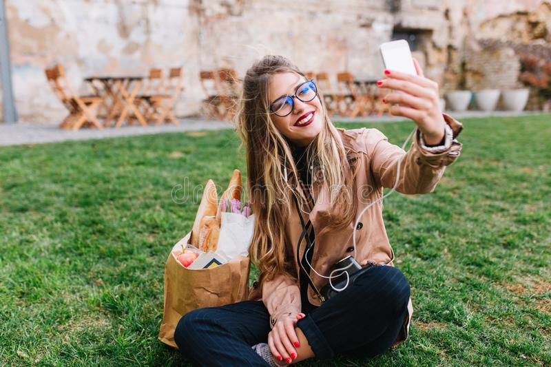 Muchacha rubia linda en los vidrios que hacen el selfie con la mano encima de sentarse en la hierba verde en parque El tomar enca fotografía de archivo libre de regalías
