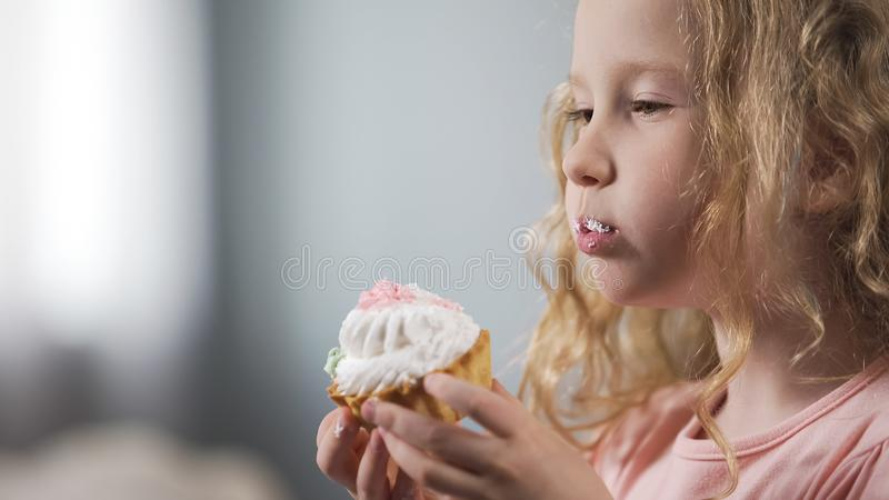 Muchacha rubia linda que come la torta cremosa, el riesgo malsano de los bocados, de la carie y de los diabéticos fotografía de archivo libre de regalías