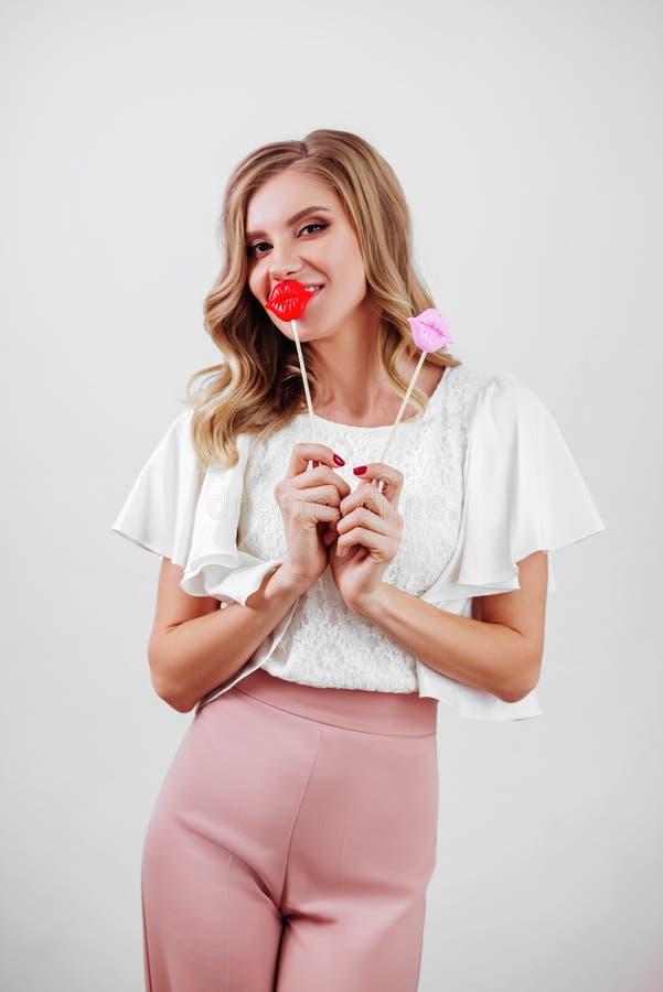 Muchacha rubia linda que presenta como una muñeca en retrato divertido foto de archivo libre de regalías
