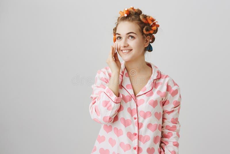 Muchacha rubia linda y blanda con los bigudíes de pelo rojos, pijamas que llevan con la plantilla del corazón, limpiando la cara  imagenes de archivo