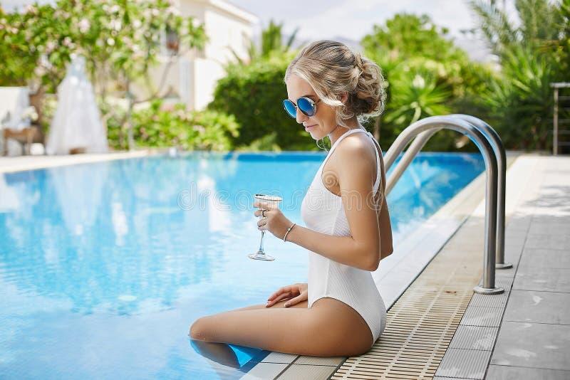 Muchacha rubia modelo joven de moda y atractiva en traje de baño, con el vidrio del champán en sus manos, presentando en la pisci fotos de archivo libres de regalías